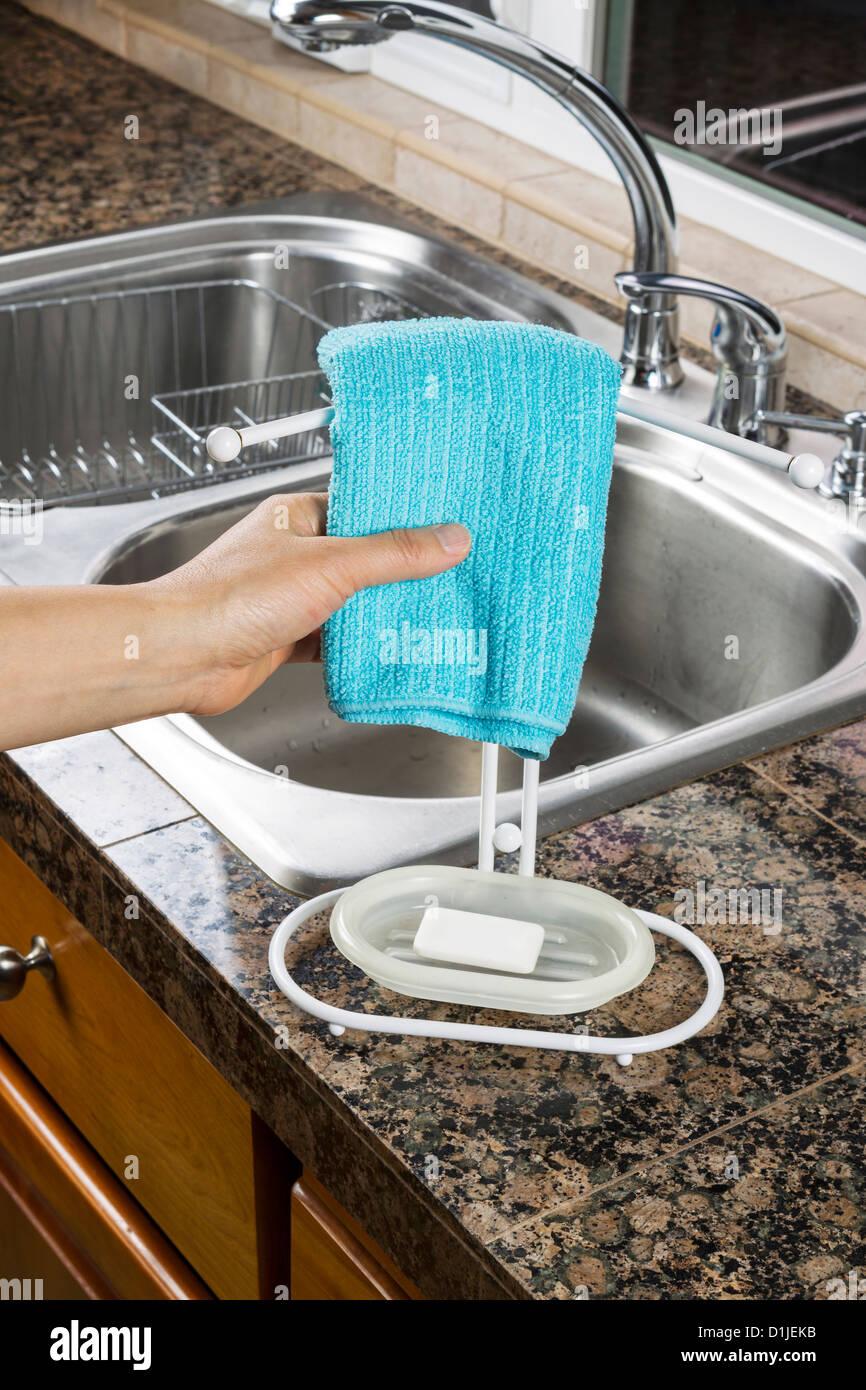 Female hand hanging microfiber dish towel on rack in kitchen ...