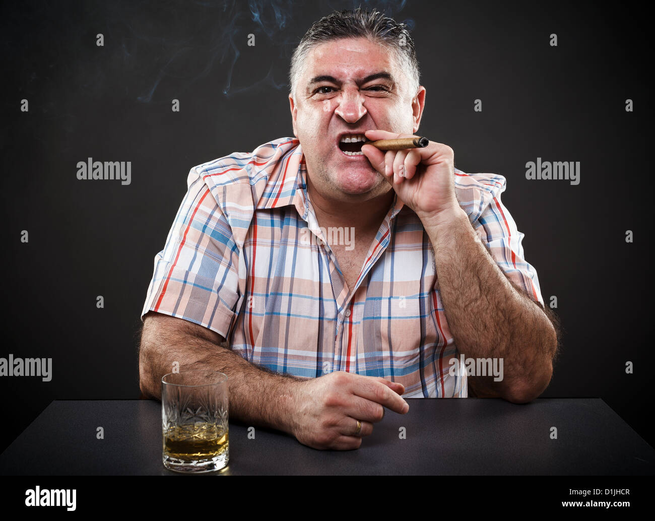 Portrait of a mature mafia man drinking and smoking while sitting at table on gray background - Stock Image