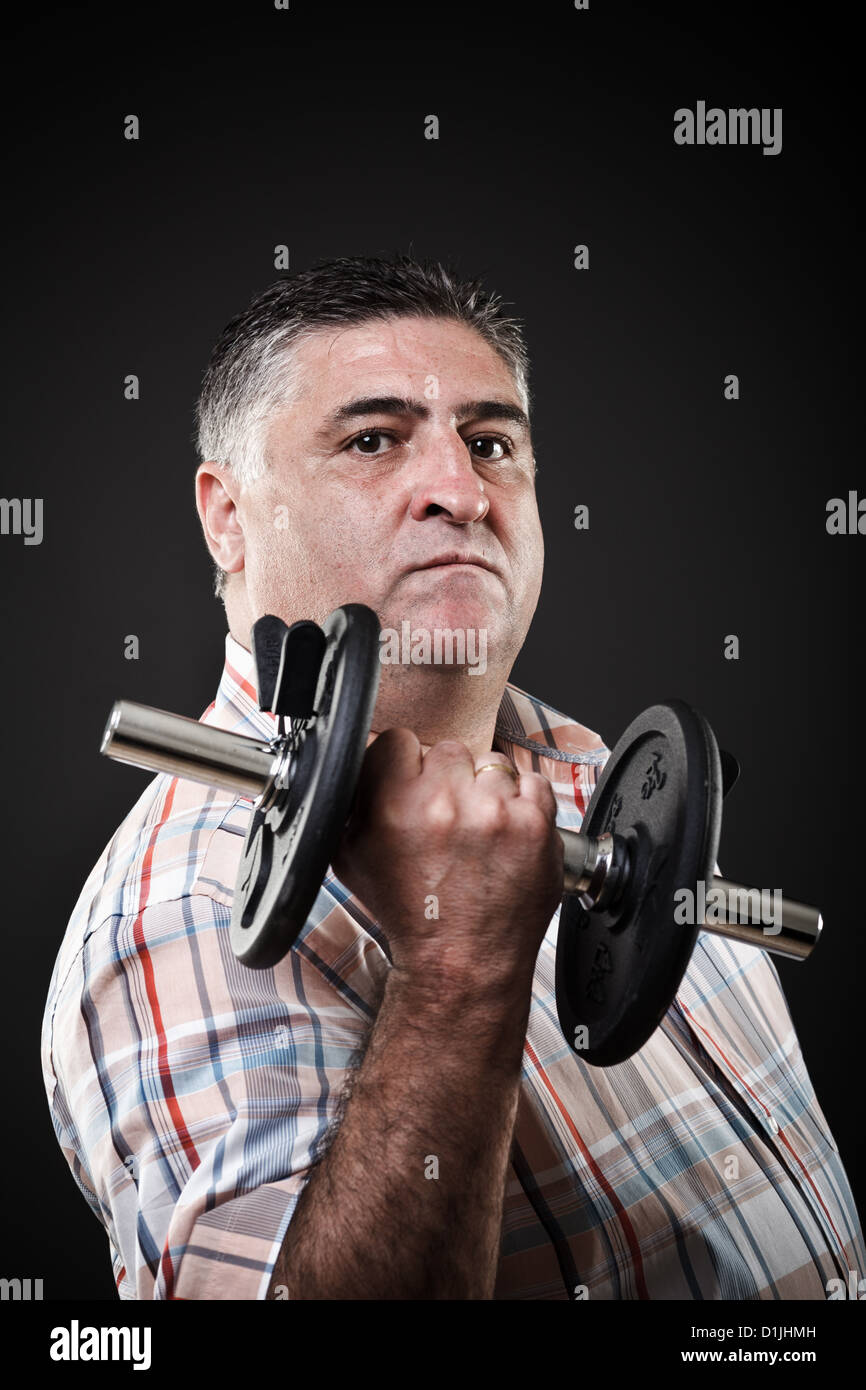 Closeup portrait of a fat man with dumbbell on gray background - Stock Image