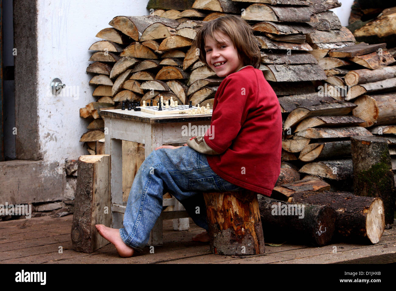 barefoot girl sitting on a wooden log and playing chess - Stock Image