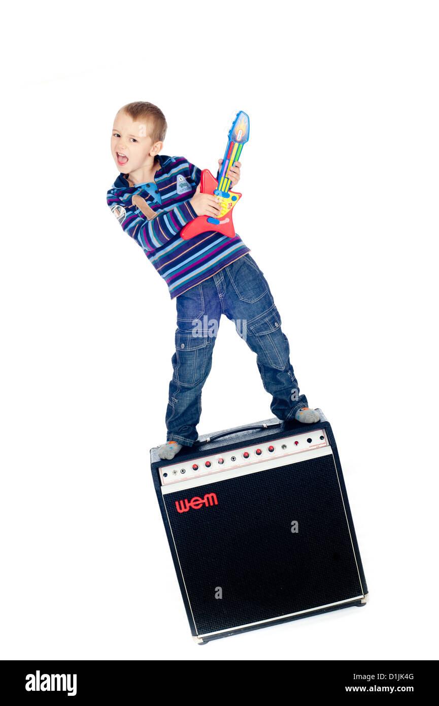 Boy playing guitar on top of amp  (© Alan Davidson) - Stock Image