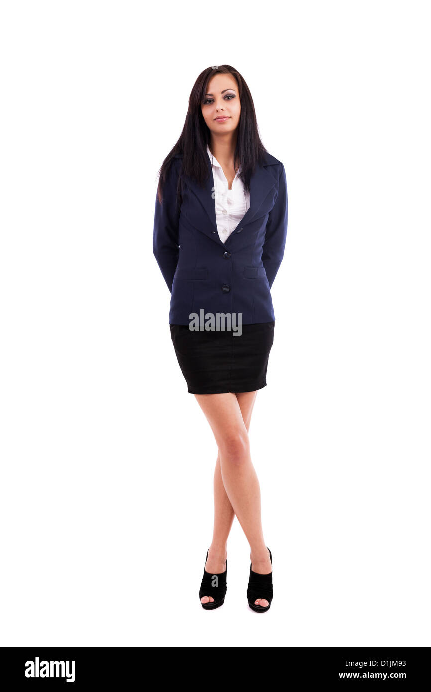 Full length portrait of a beautiful latin businesswoman standing with crossed legs isolated on white background - Stock Image