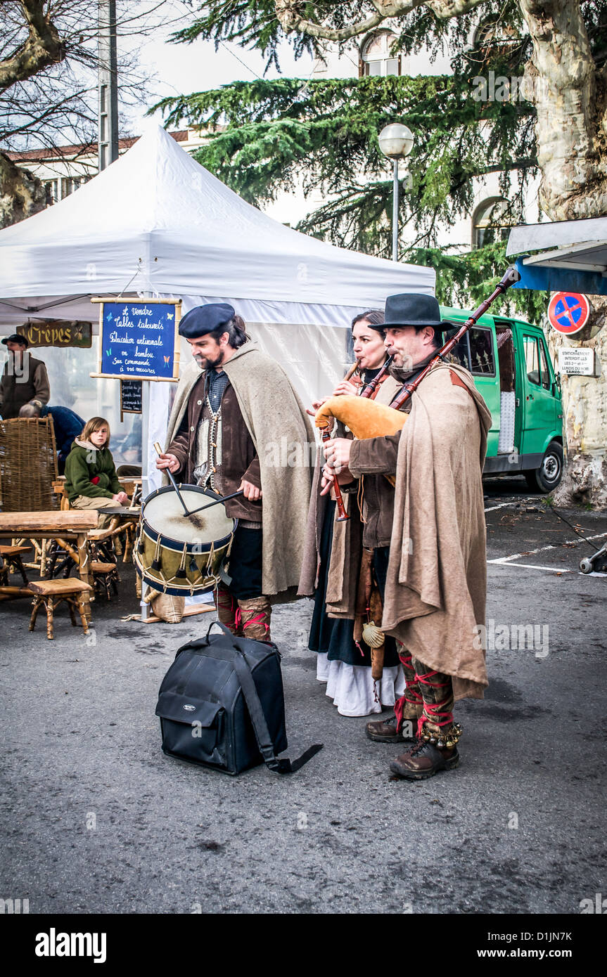Three Bethmale musicians wearing traditional capes as they play folk music in St. Girons, Midi-Pyrenees, France. Stock Photo