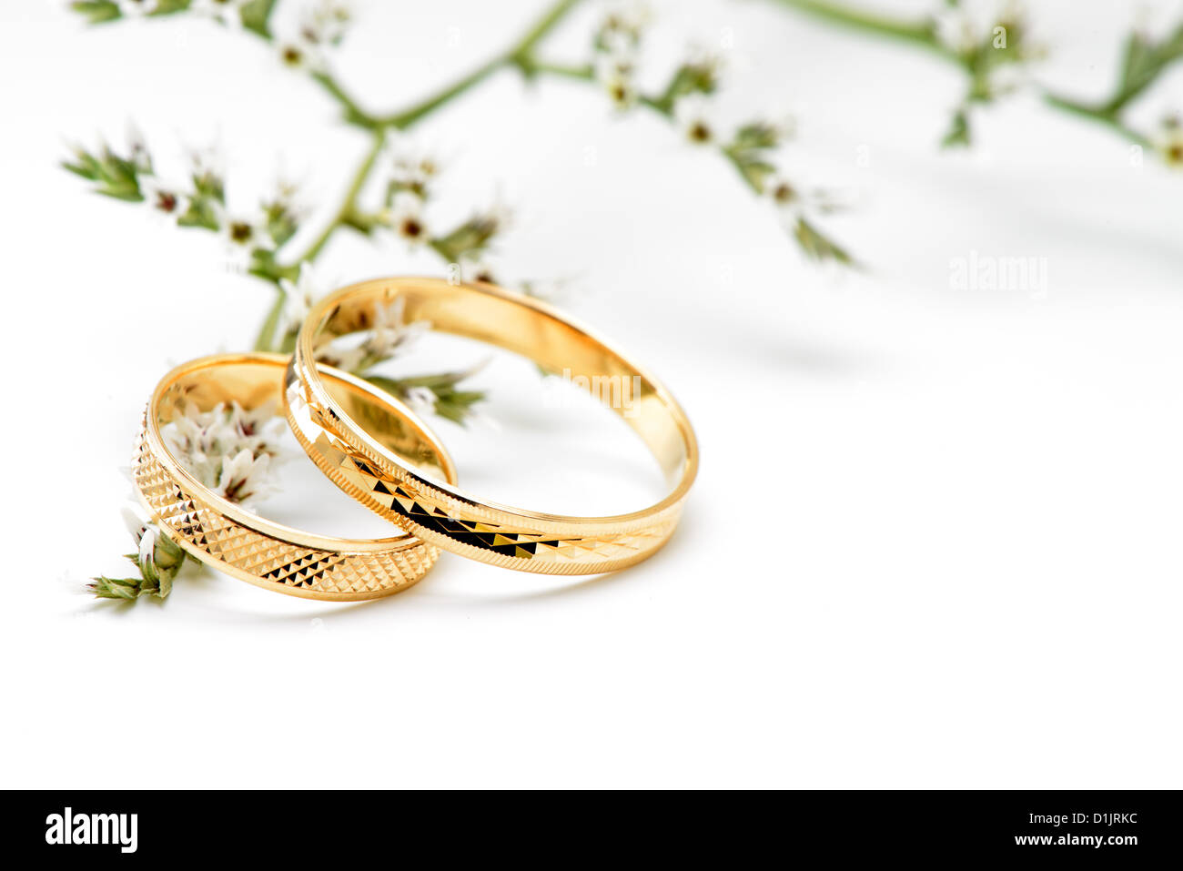Gold Wedding Rings And Branch Flowers Isolated On White Background