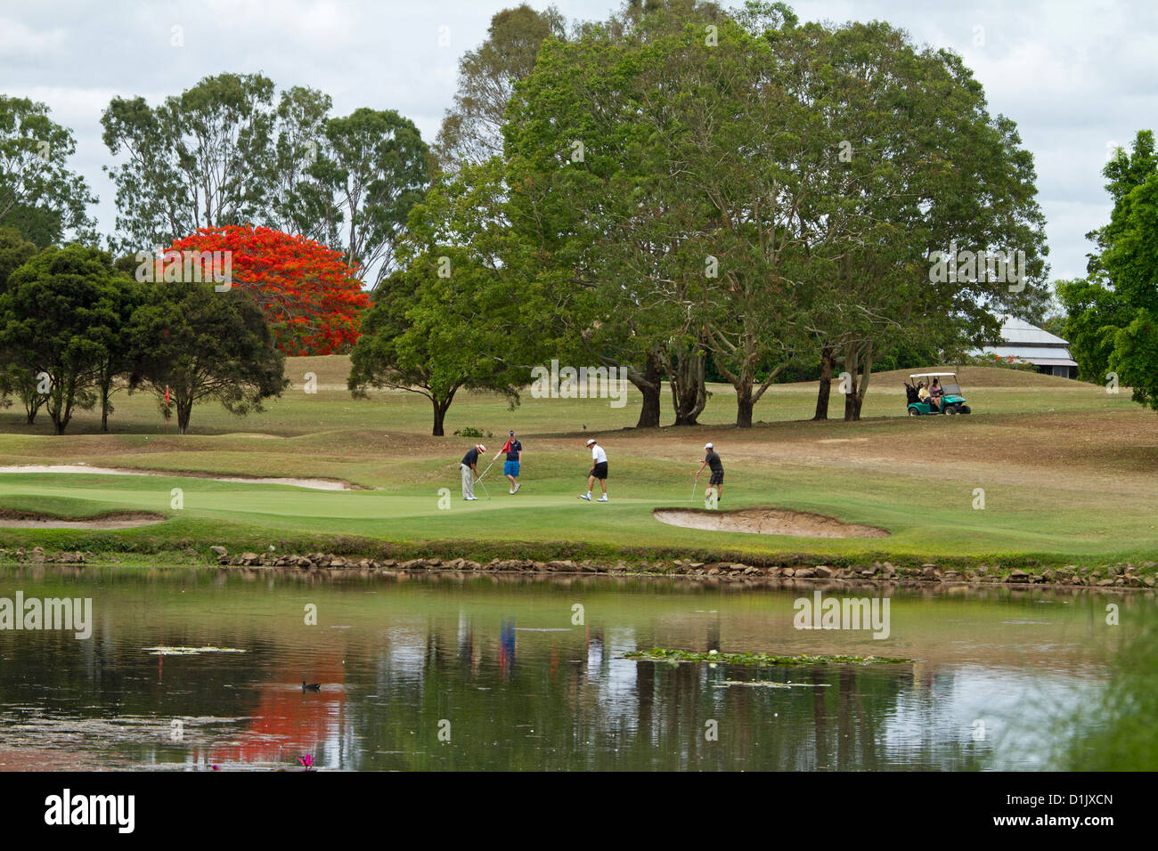 Group of golfers playing beside lake at picturesque golf course with trees and people reflected in water - Stock Image