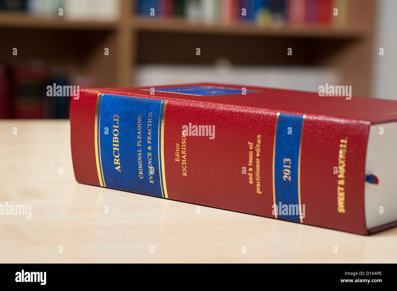 Close up photo of Archbold 2013 law book sitting on desk in office with book shelves of law books. - Stock Image