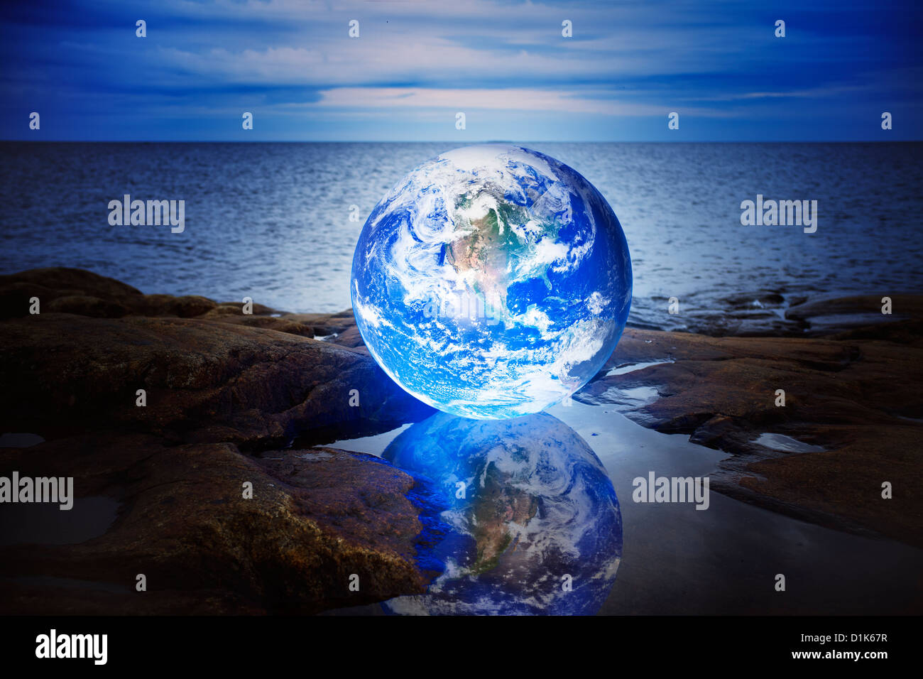 Conceptual image of a Glowing earth in a puddle at sea. Earth image provided by NASA. - Stock Image
