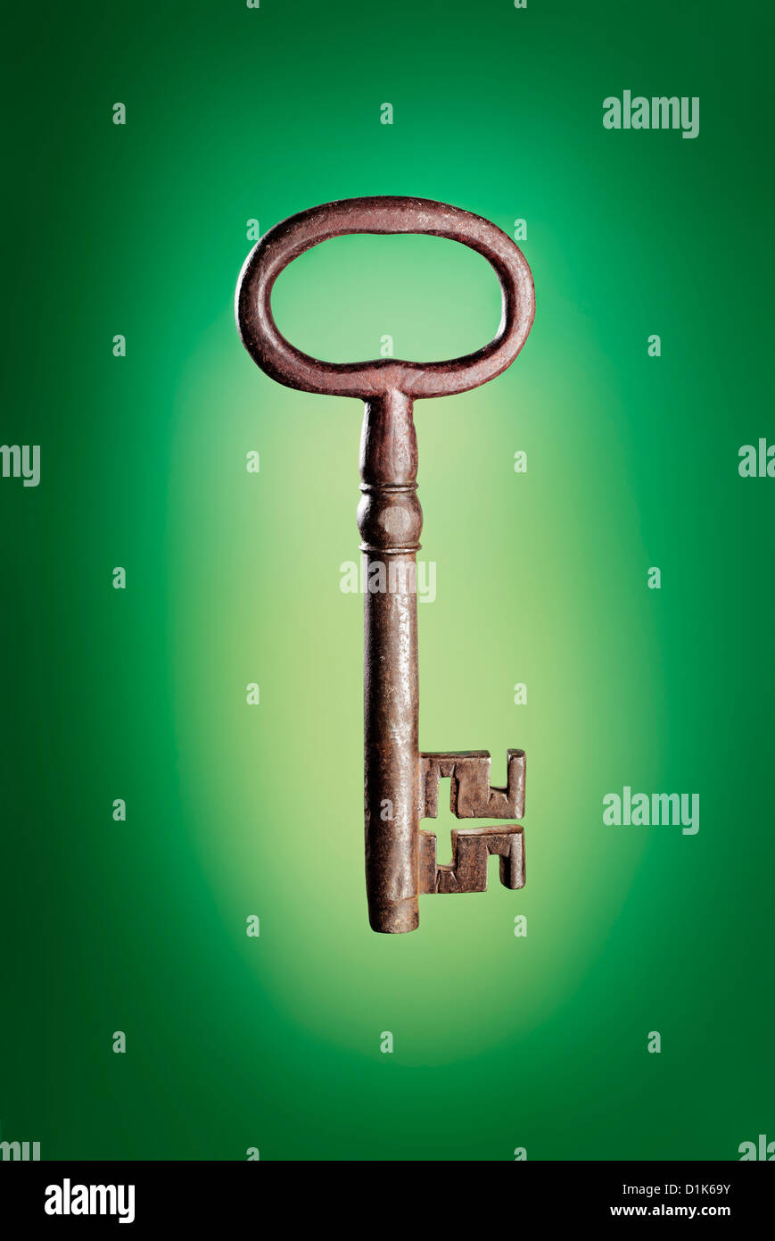 Old big antique key on green background. - Stock Image