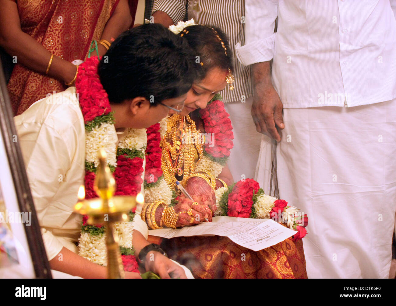 bride and groom signing marriage certificate during an indian hindu wedding or kerala hindu wedding, kerala,south Stock Photo