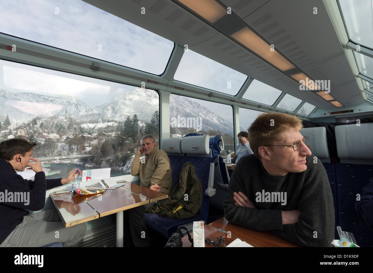 Passengers on the Glacier Express Train look out onto the mountains near Brig, Switzerland. - Stock Image