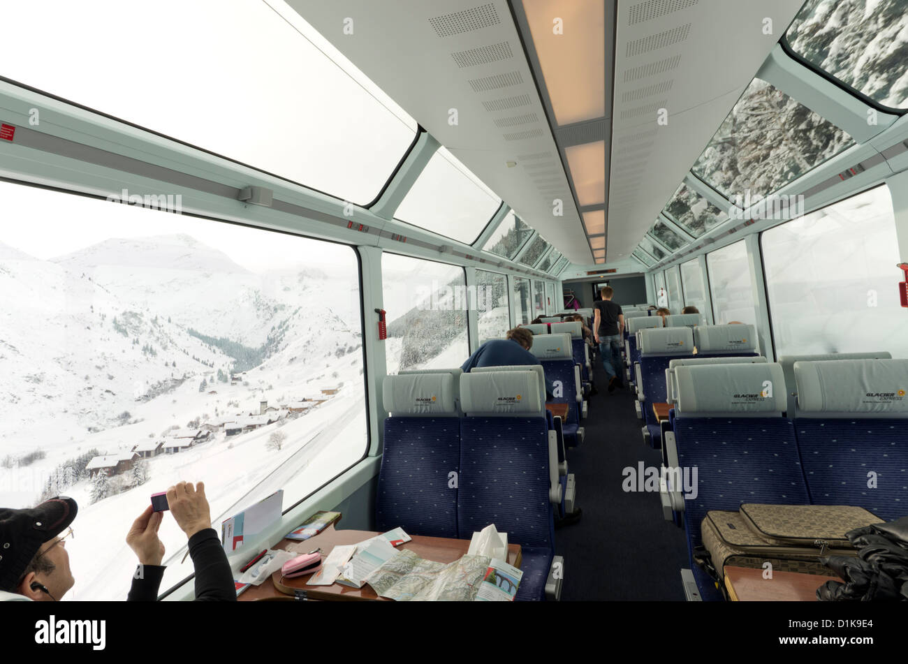 Passengers on the Glacier Express Train look out onto the mountains near Oberwald, Switzerland. - Stock Image