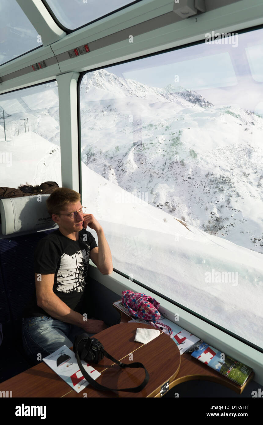A passenger relaxes on the Glacier Express Train with a stunning view onto the mountains near Andermatt, Switzerland - Stock Image