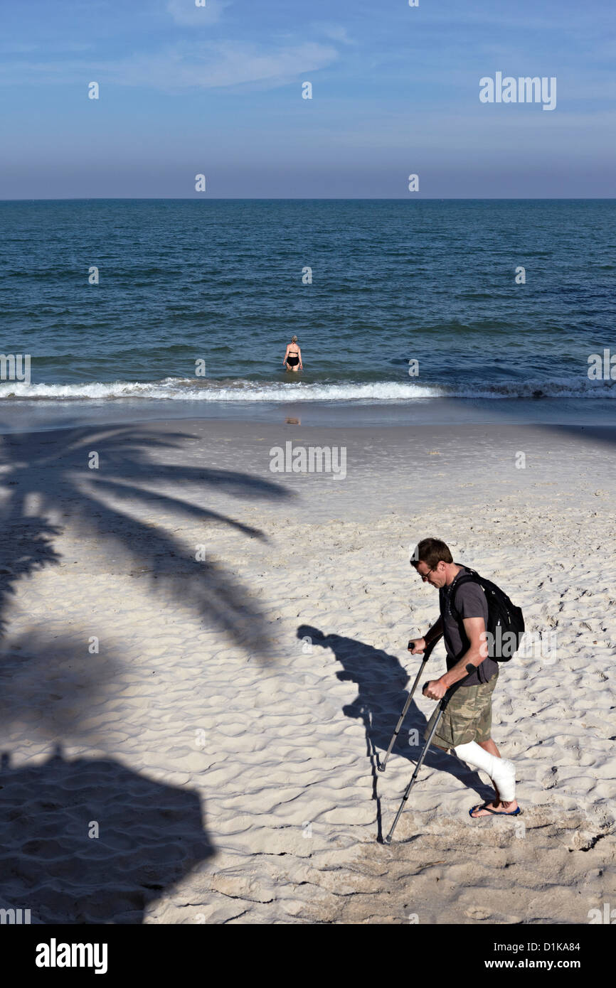 Conceptual image of a man on crutches with a broken leg following a holiday incident. Highlighting the need for - Stock Image