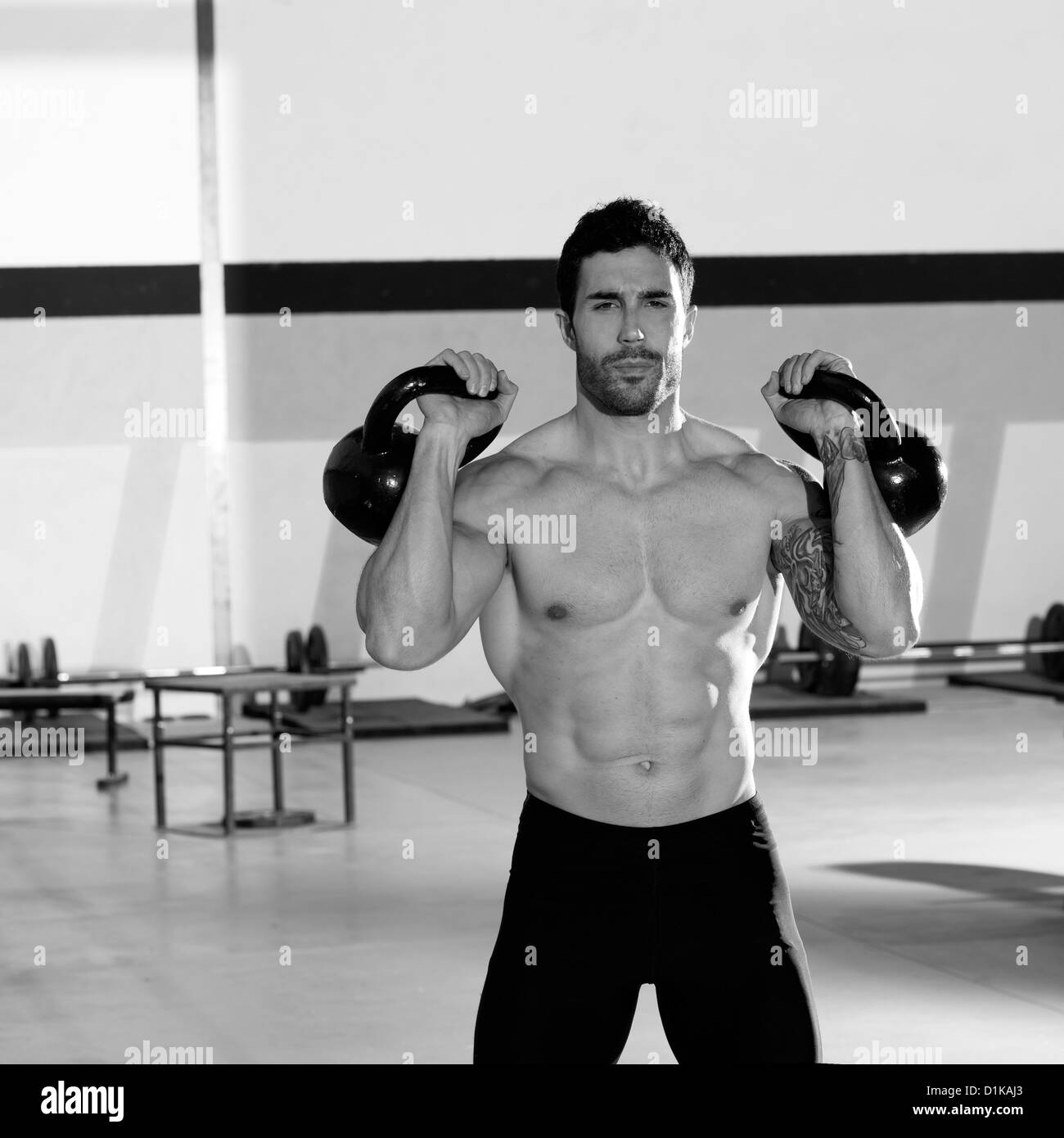 crossfit man lifting kettlebell workout exercise at gym stock photo