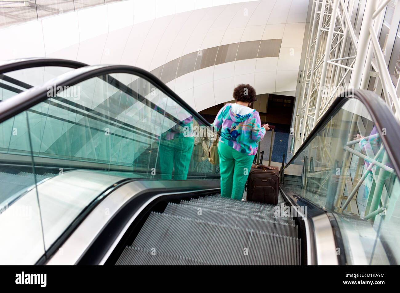 An overweight woman in tacky colors rides down the escalator at an airport - Stock Image
