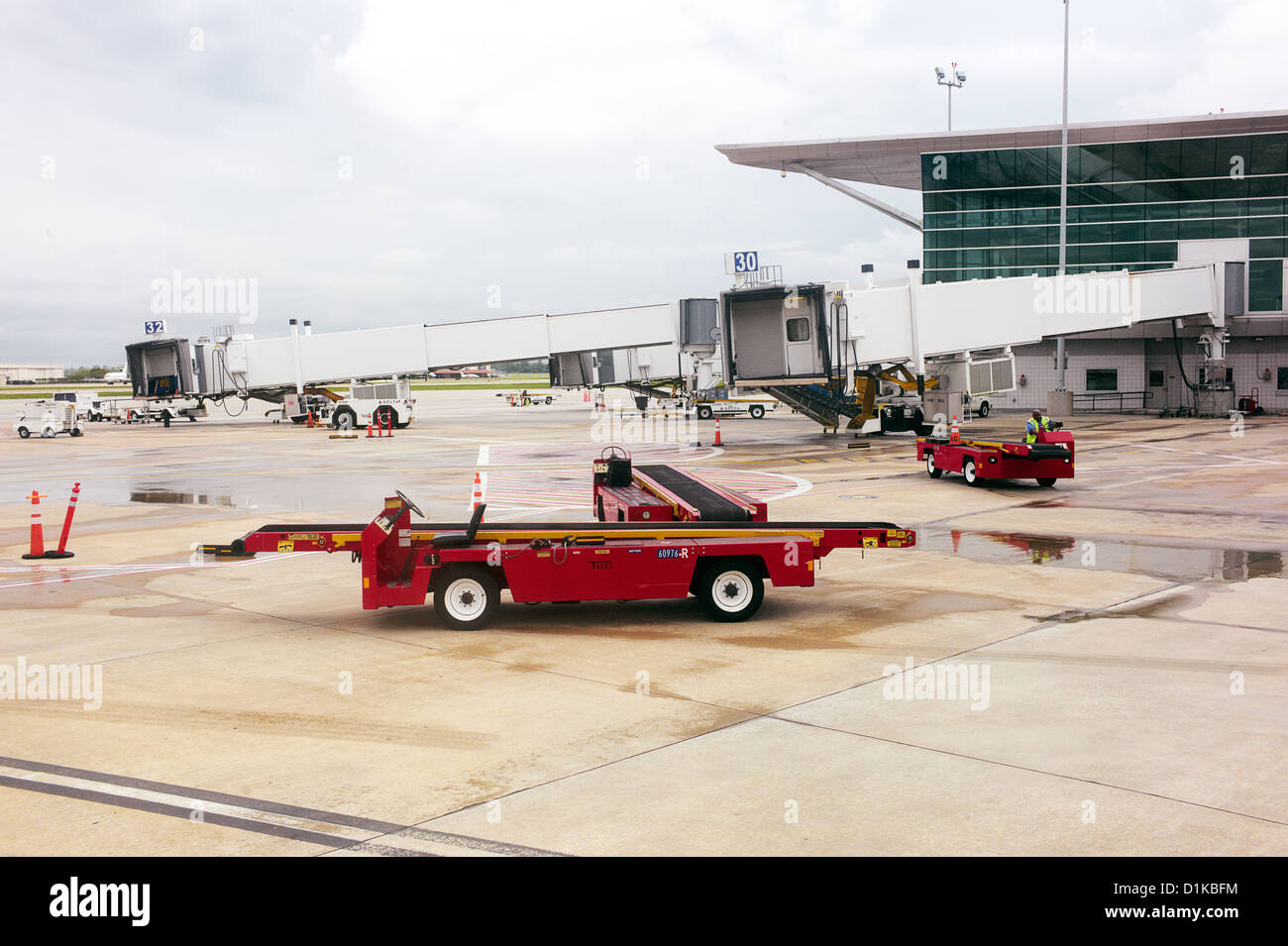 A red baggage loading car on an airport tarmac - Stock Image