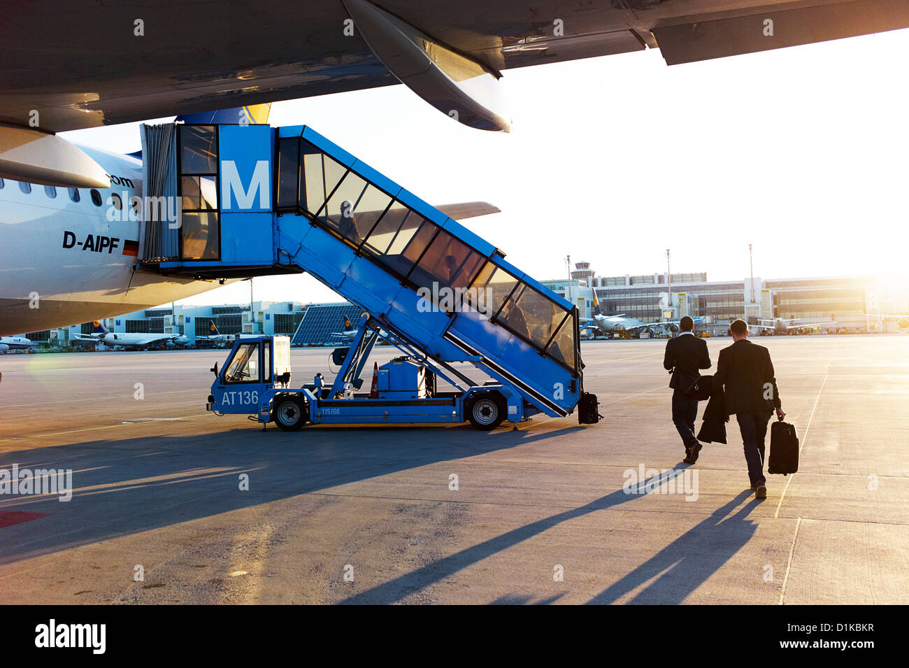 Businessmen and travelers board a plane on the tarmac at sunset - Stock Image