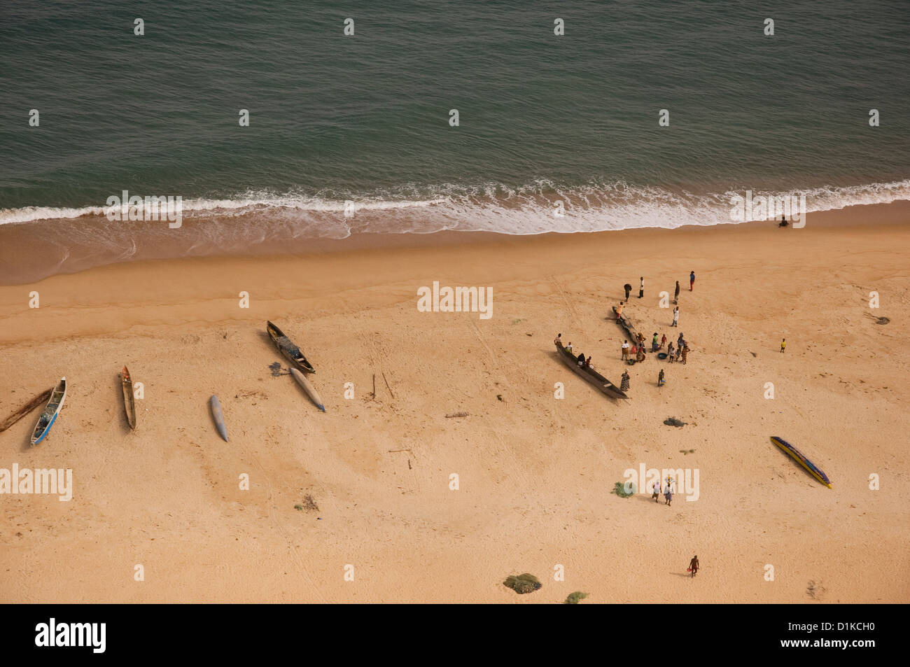 Image of fishermen, women, pirogues and nets sprawled across the beach in anticipation for the days catch, Liberia. - Stock Image