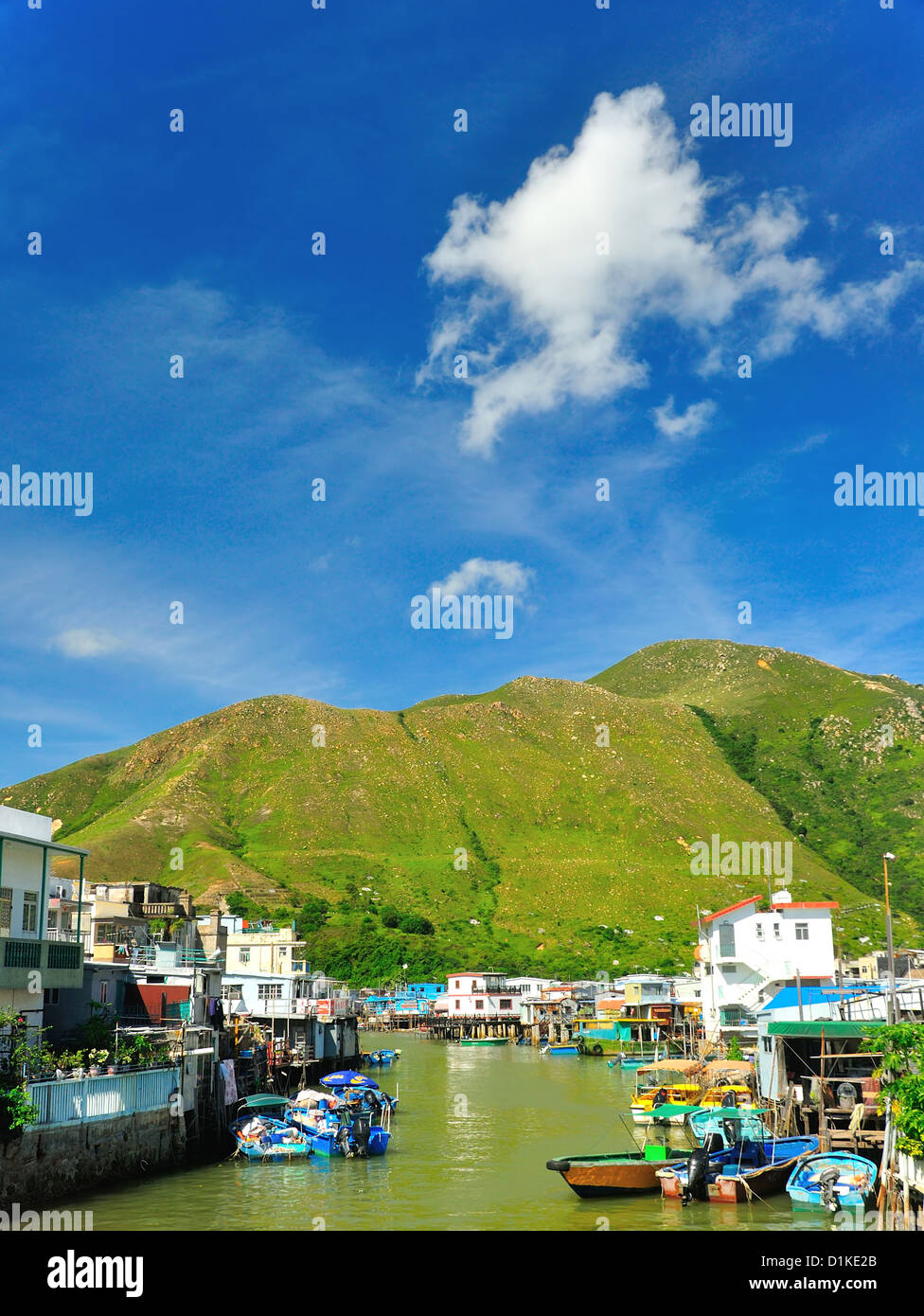 Tai O, an fishing village in Hong Kong. With green hill and blue sky - Stock Image