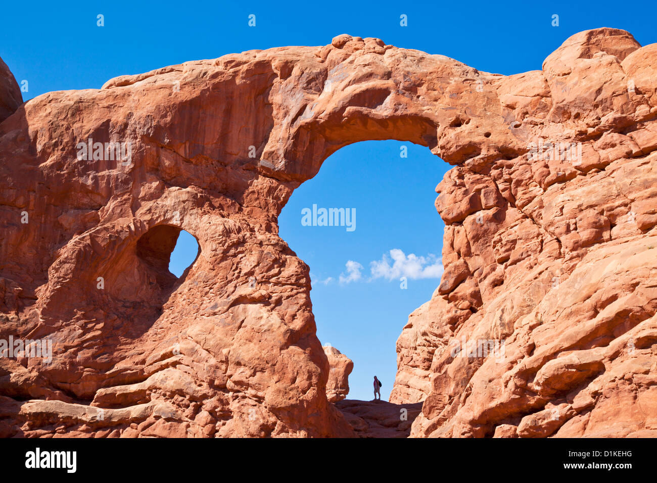 Tourist silhouetted in Turret arch in The Windows section Arches National Park near Moab Utah USA United States Stock Photo