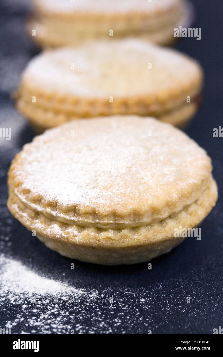 Freshly baked mince pies on a slate serving plate. - Stock Image