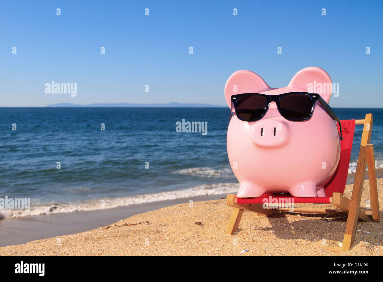 Pink piggy bank on a beach in a deck chair wearing sunglasses with golden sand a blue ocean and vivid blue sky - Stock Image