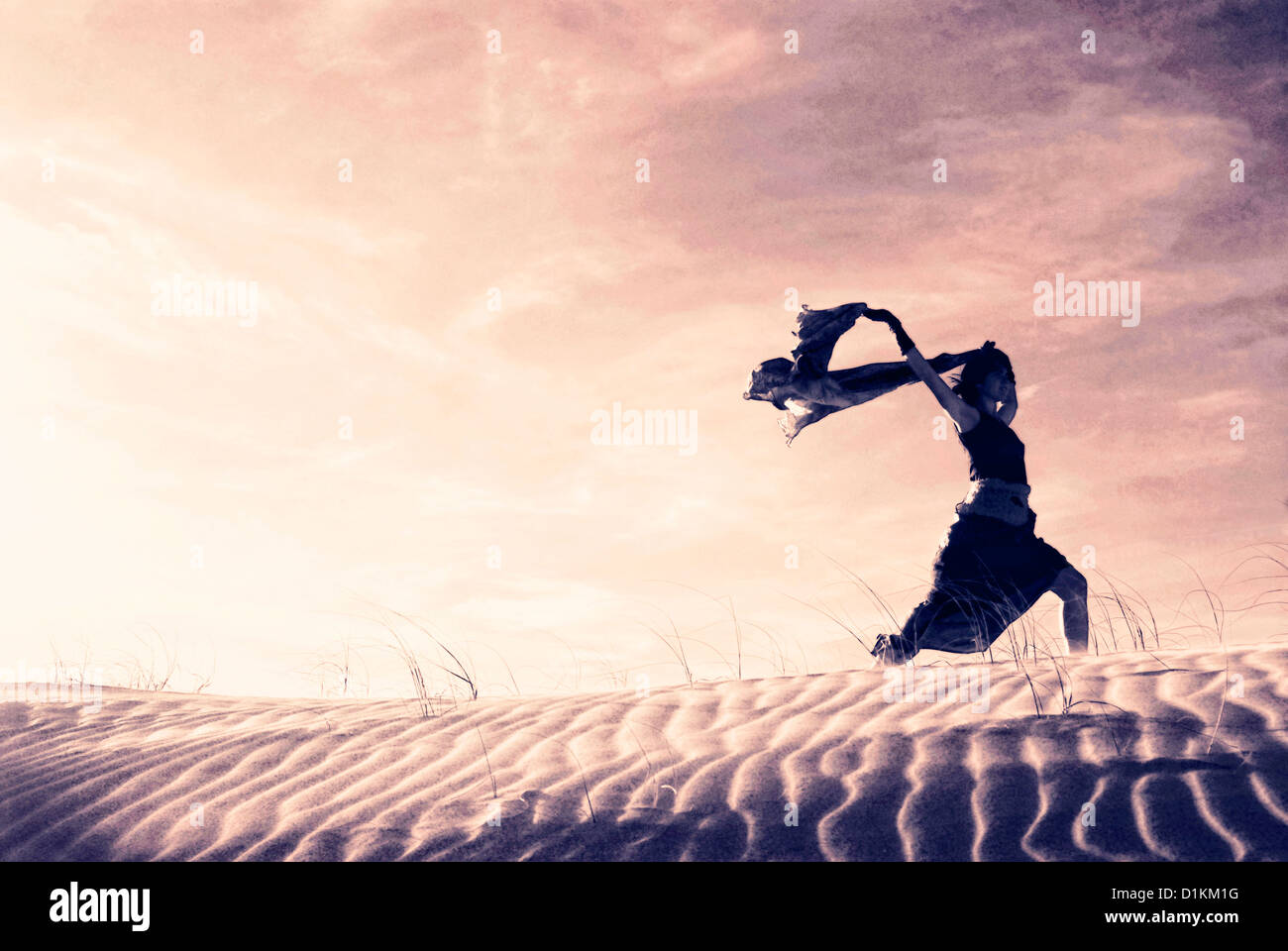 Silhouette of a woman holding a blowing scarf in the dunes. - Stock Image