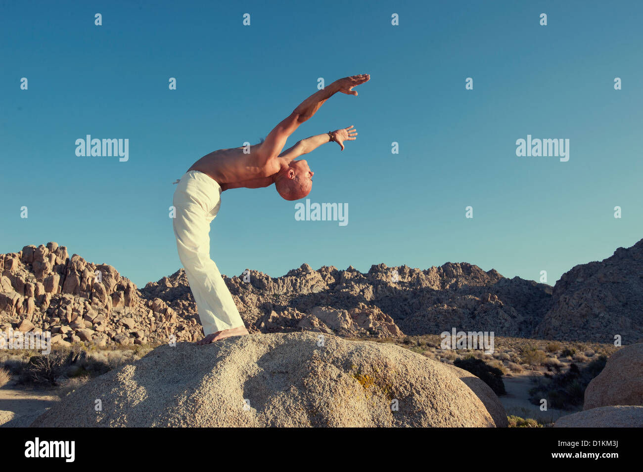 Man in yoga posture outdoors in the forest. - Stock Image