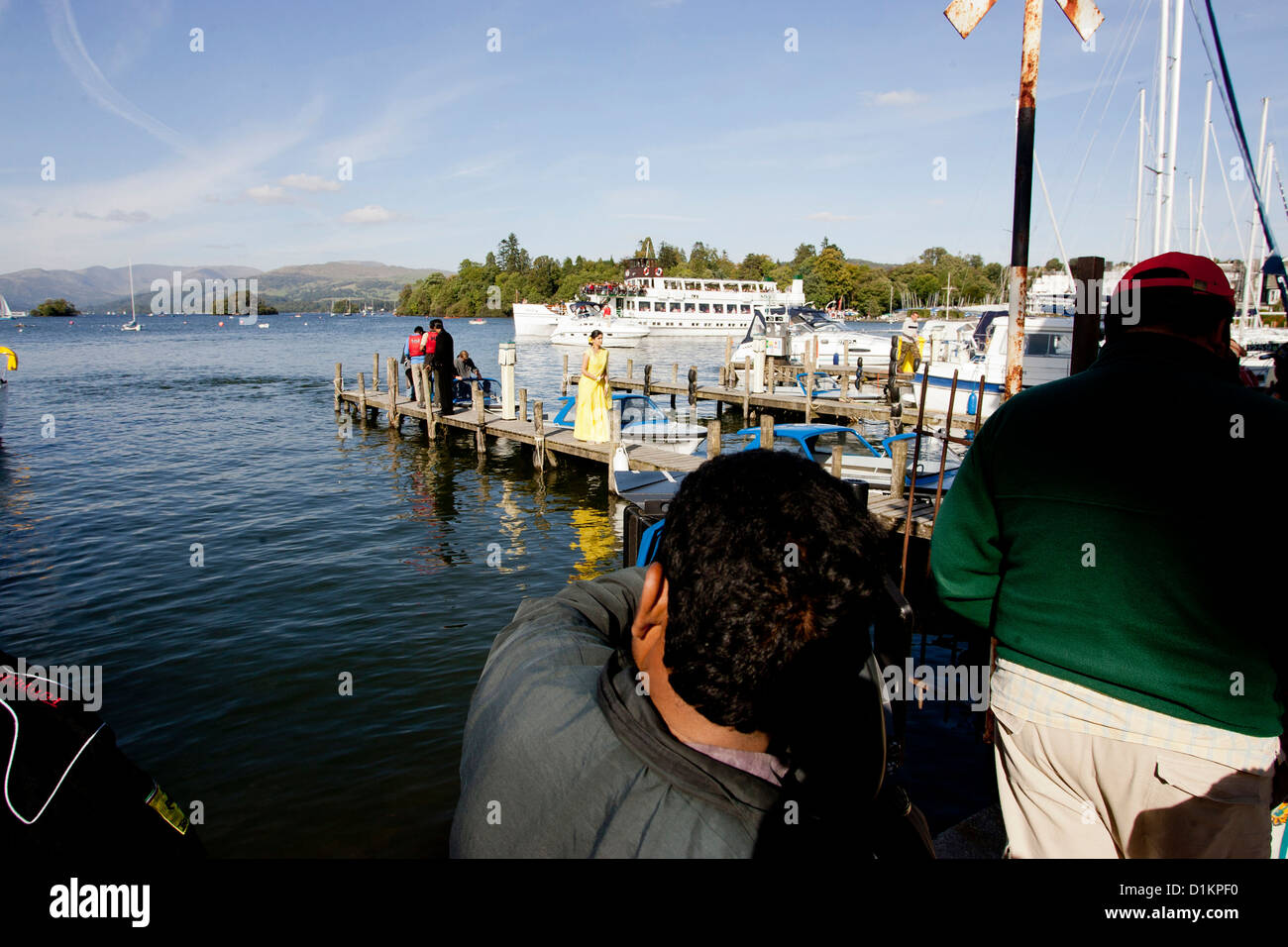 The MV Swan ,  originally steam , passenger ferry in background on Lake Windermere while Bollywood film is shot - Stock Image