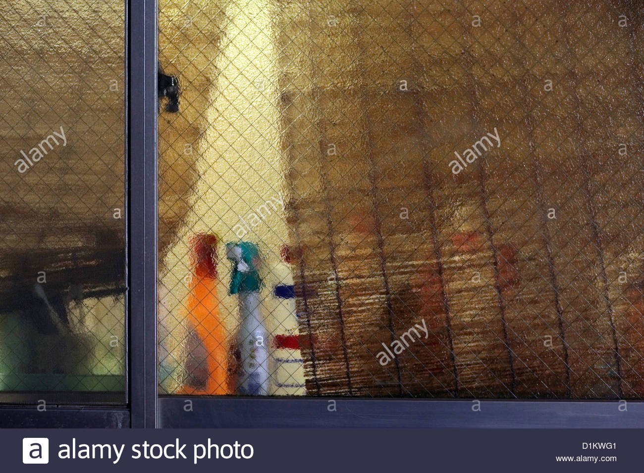 kitchen window with cleaning bottles during night - Stock Image