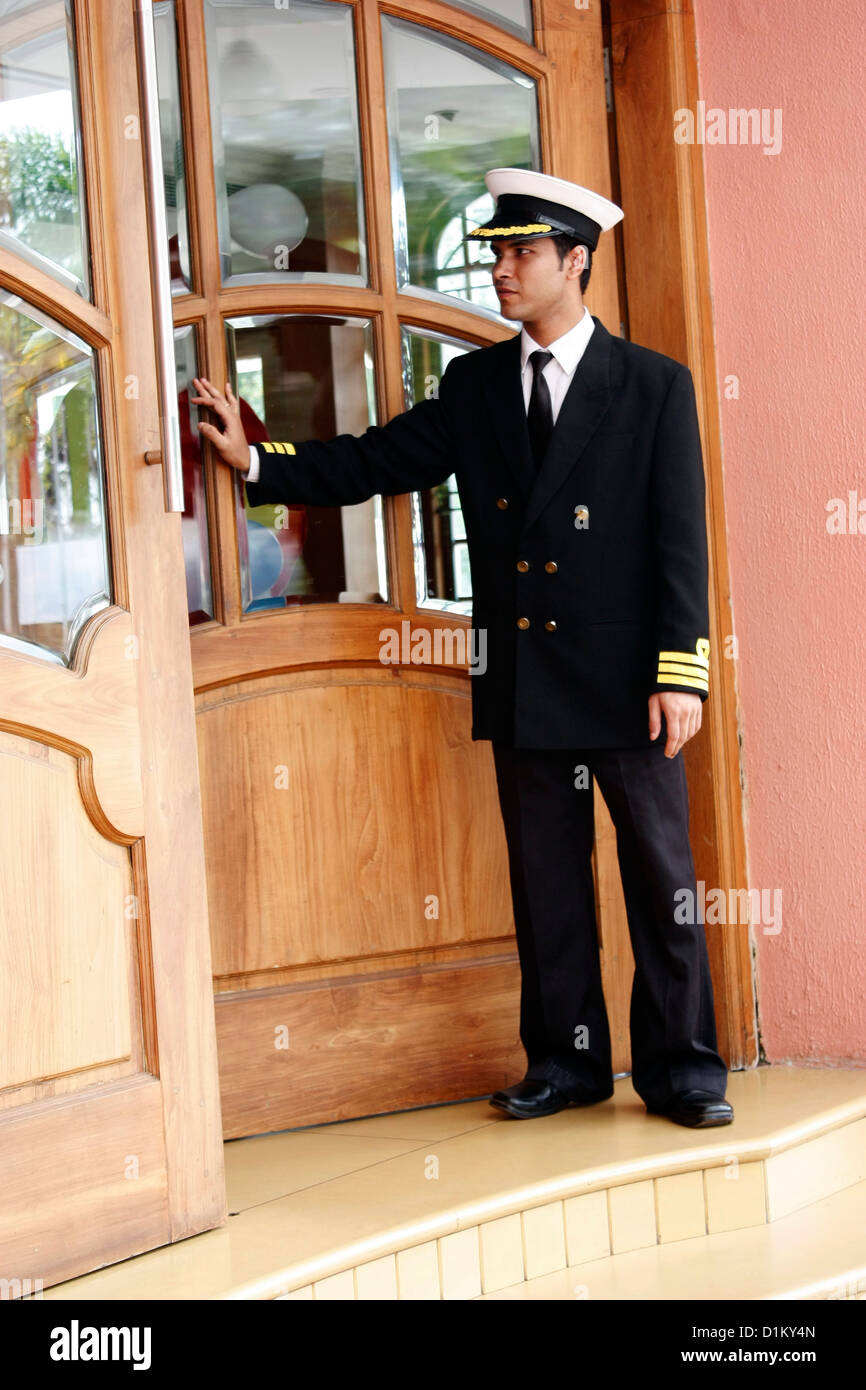 A doorkeeper opening the door for the guests to enter exit out of a building - Stock Image