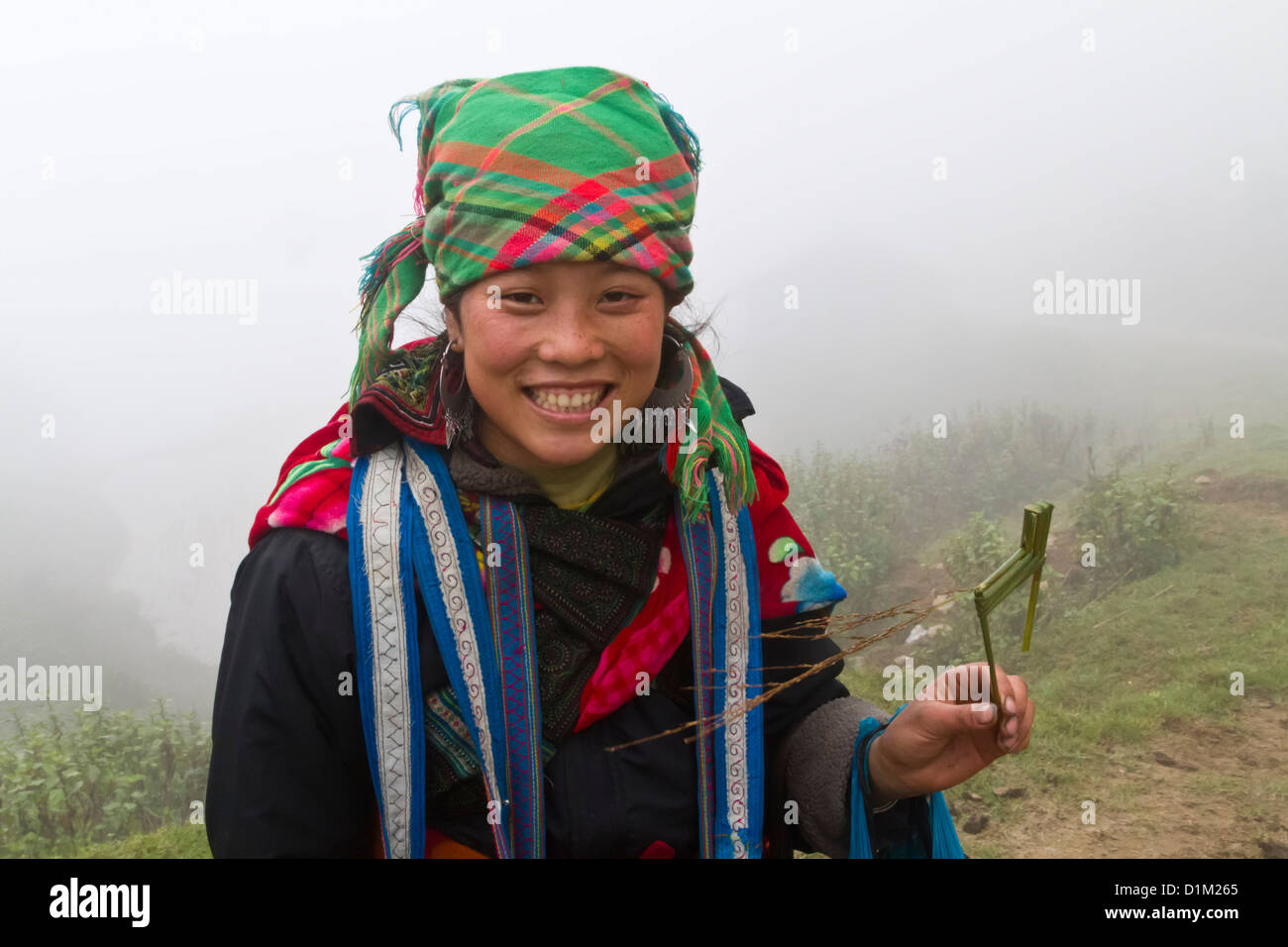 Hmong woman with grass sculpture of a horse, in winter clouds in Sapa, near China border in Vietnam. - Stock Image