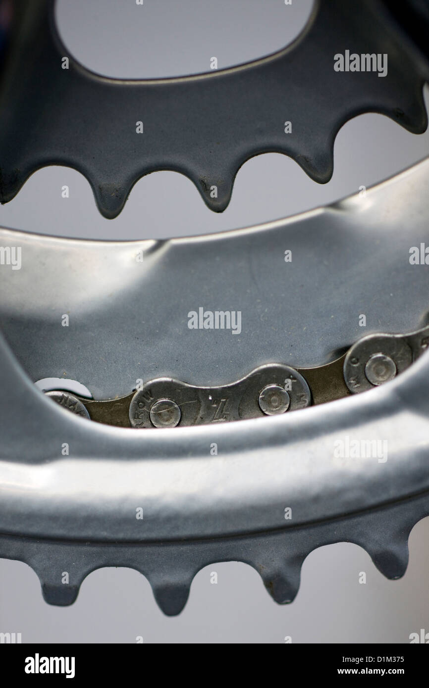 Close up of crankset showing chainring and bike chain, parts of bicycle - Stock Image