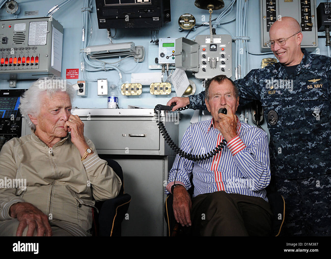 Former President George H. W. Bush, center, addresses U.S. Sailors using the public address system during a visit to the aircraft carrier USS George H. W. Bush (CVN 77) in the Atlantic Ocean Jan. 14, 2010. Accompanying Bush are wife Barbara Bush, left, an Stock Photo