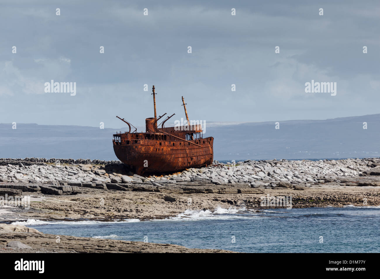 The cargo vessel Plassey shipwrecked off Inishee  Ireland in the 1960s. Only its rusted hulk remains on the rocks - Stock Image