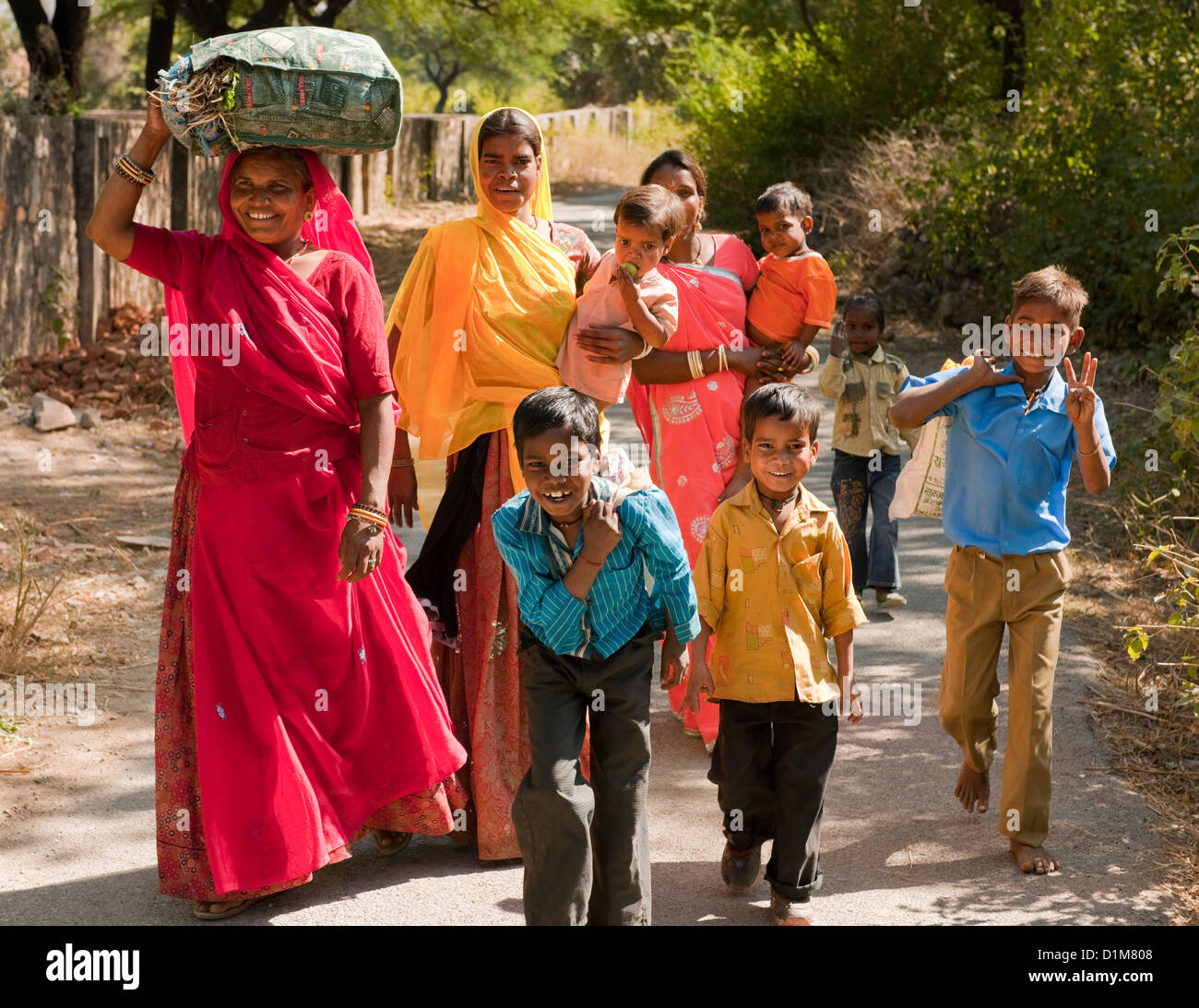 A happy smiling colorful Indian family group of women boys girls and a baby return from shopping on a quiet road - Stock Image