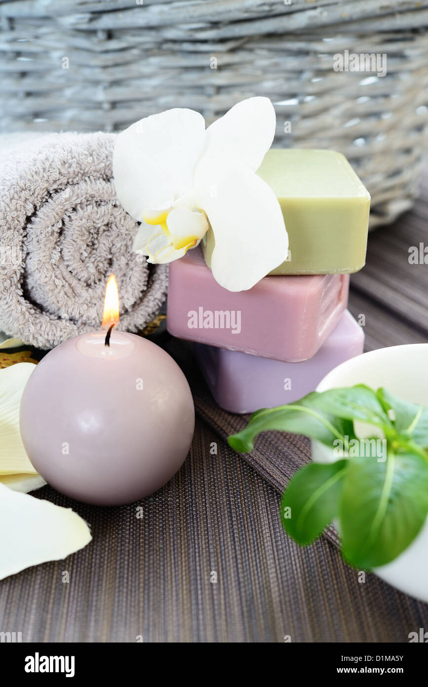 Spa and wellness setting with natural soap, candles and towel. Beige dayspa - Stock Image
