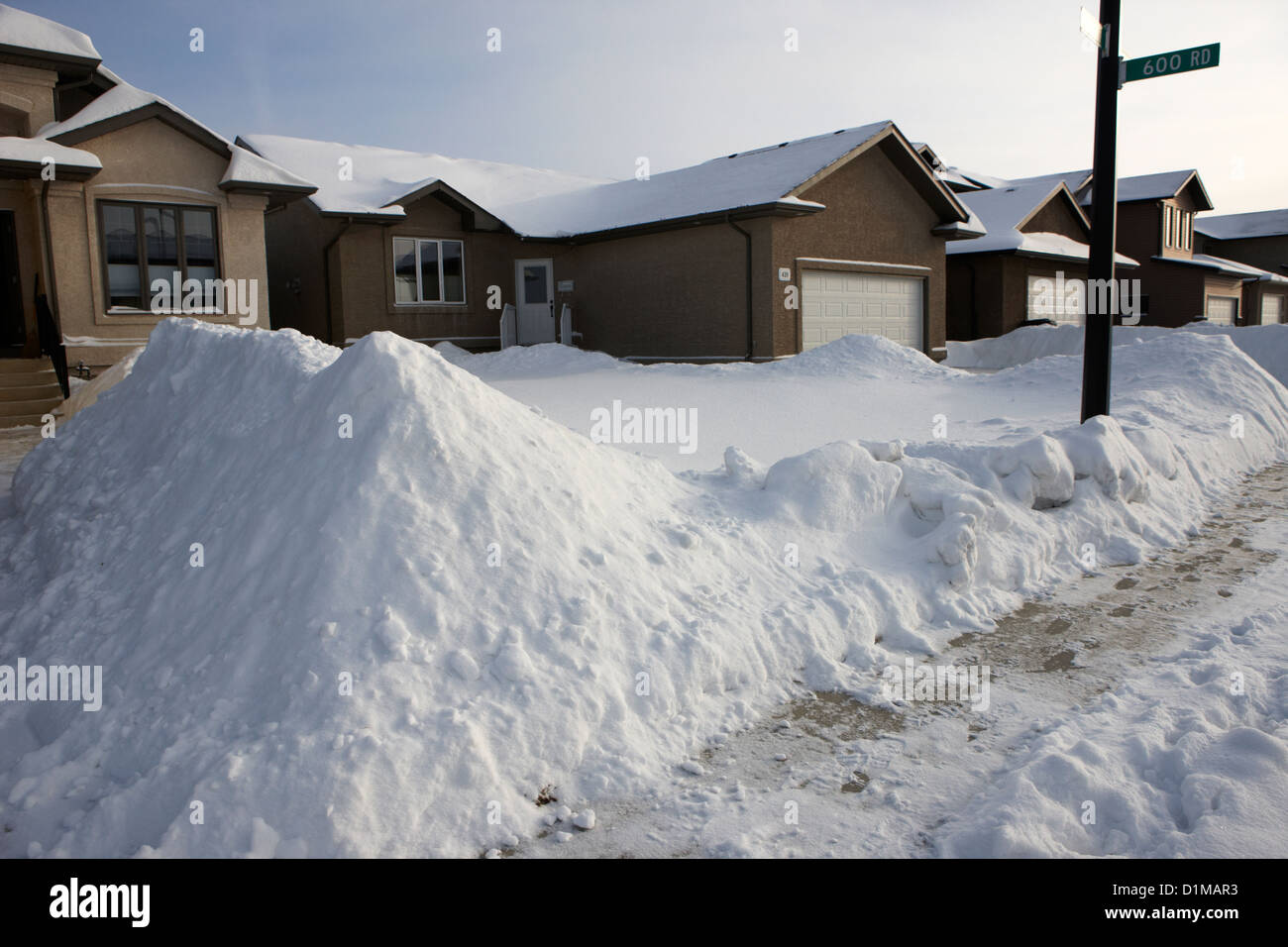 piles of cleared snow outside upmarket residential street during winter Saskatoon Saskatchewan Canada - Stock Image