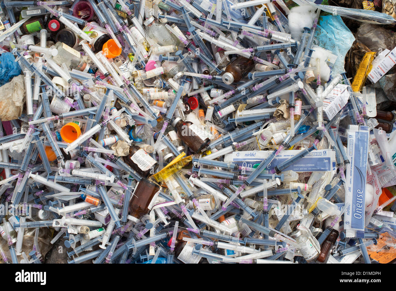 Hypodermic syringes with needles dumped in rubbish in the Indian countryside. Andhra Pradesh, India - Stock Image