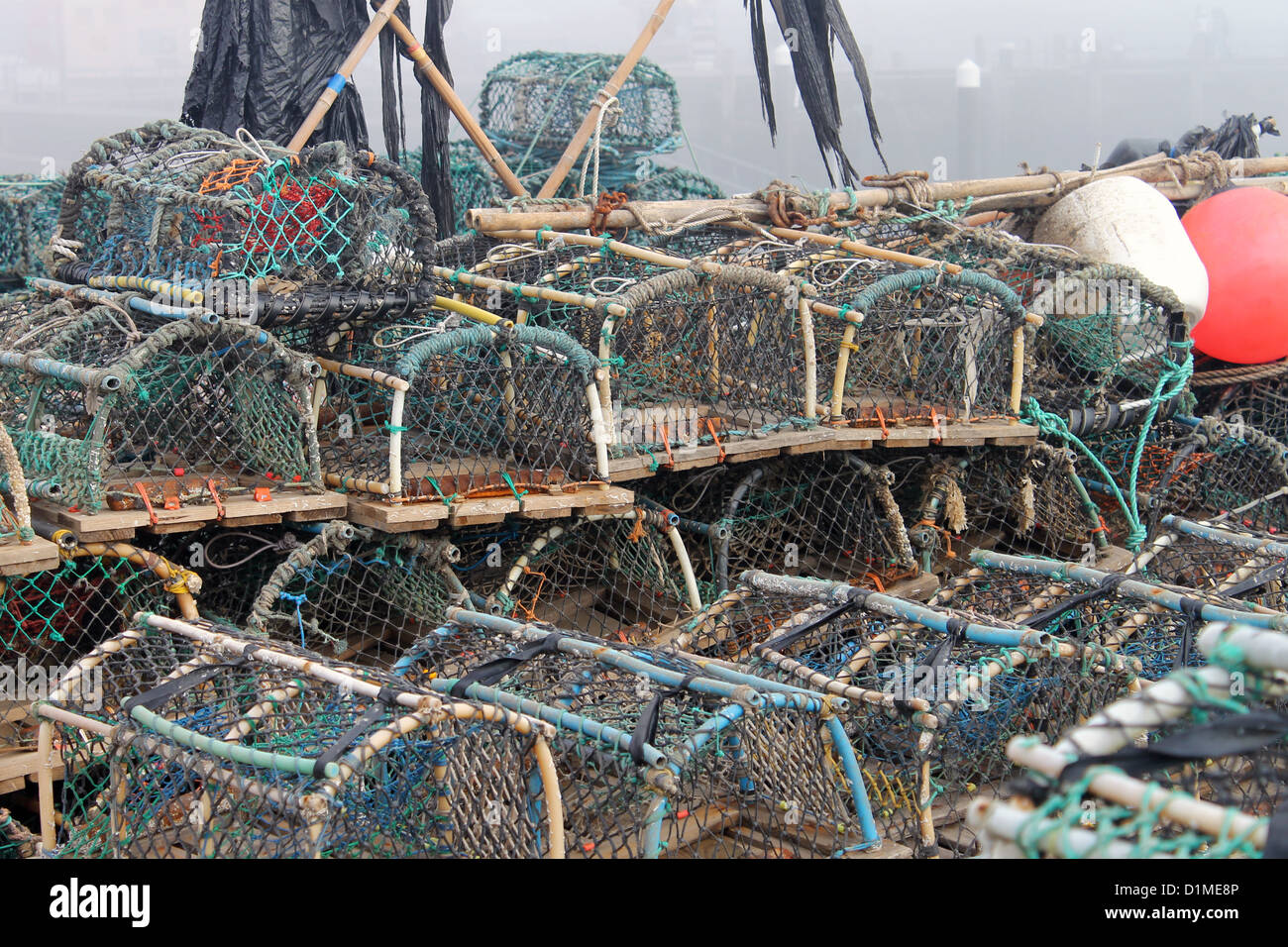 Lobster pots and creels in Scarborough harbor with fog background, England. - Stock Image
