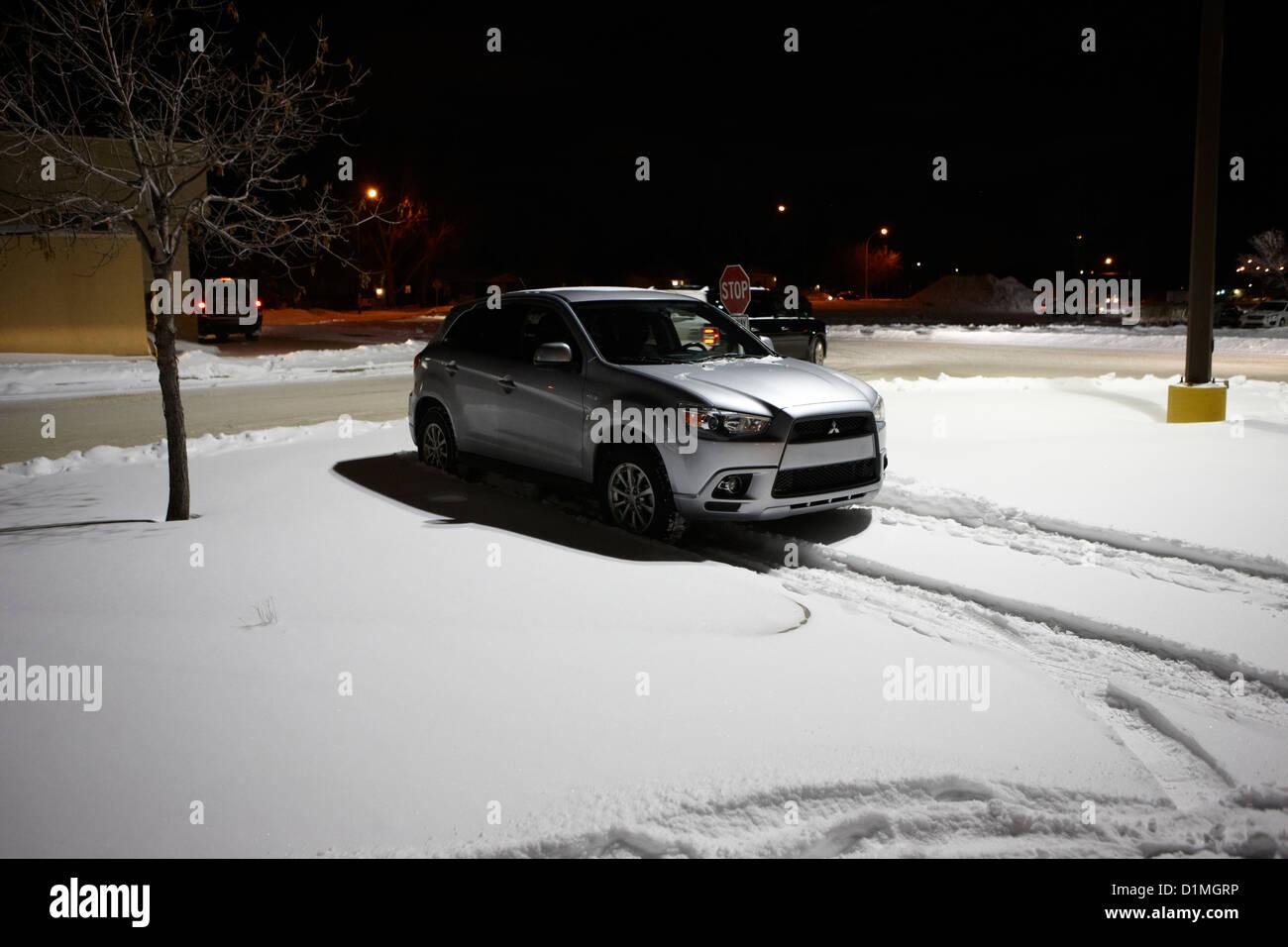 car parked in deepening snow in outdoor parking lot in Saskatoon Saskatchewan Canada - Stock Image