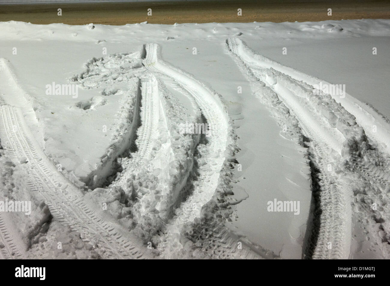 parked car tyre tracks in the snow in a parking lot Saskatoon Saskatchewan Canada - Stock Image