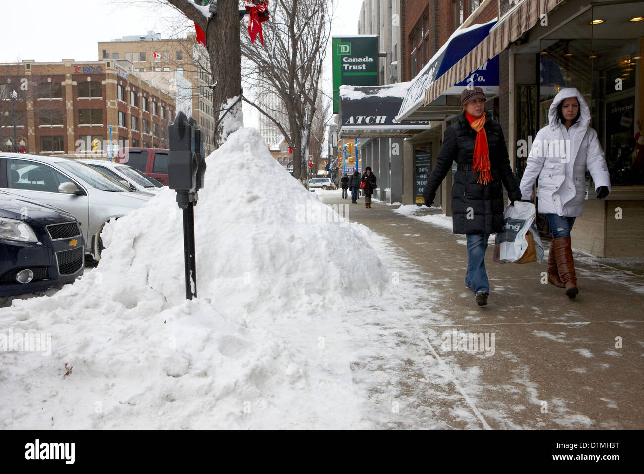 people walking along clear sidewalks in downtown city street Saskatoon Saskatchewan Canada - Stock Image