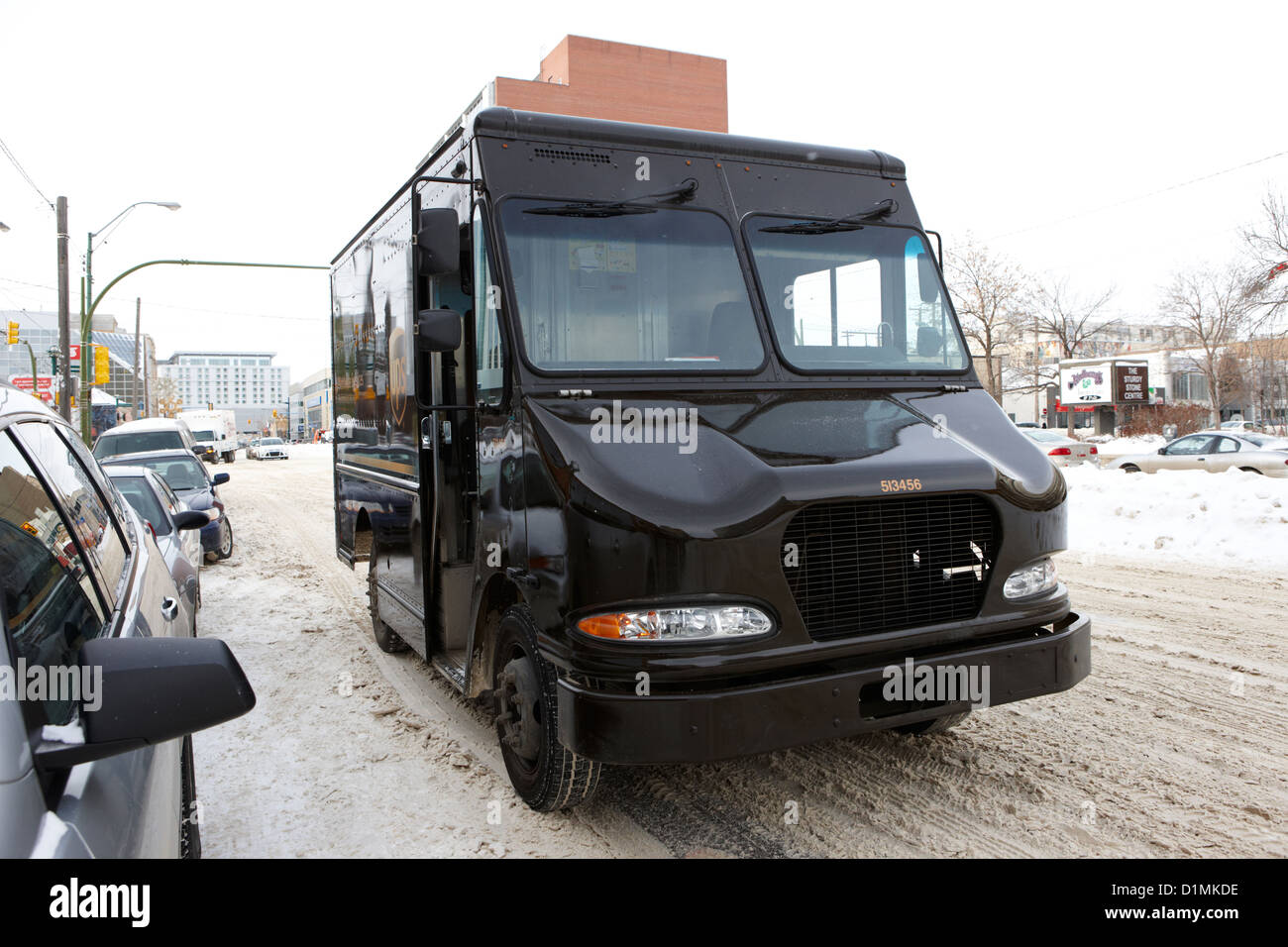 ups delivery truck double parked on street in cold weather Saskatoon Saskatchewan Canada - Stock Image
