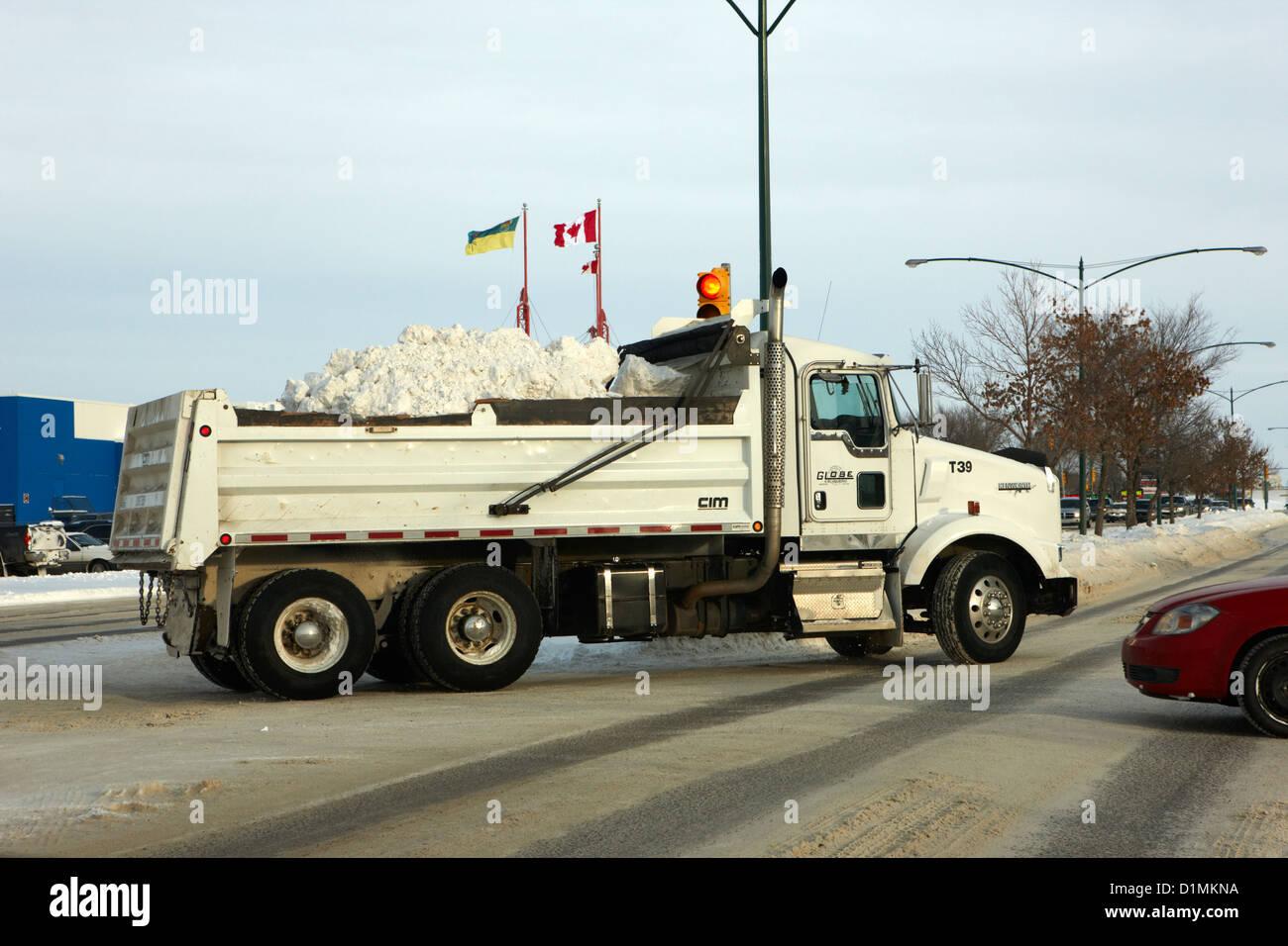municipal city dump truck taking away snow cleared from parking lots and roads in Saskatoon Saskatchewan Canada - Stock Image
