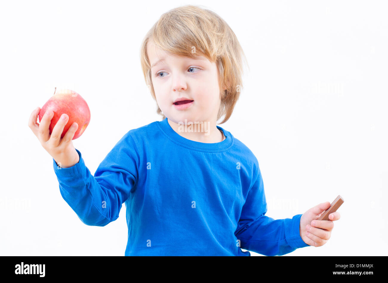 A perplexed blond boy fighting with food temptation - Stock Image