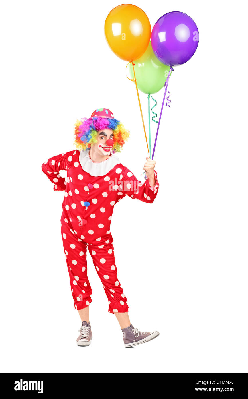 Full length portrait of a male clown in costume holding bunch of balloons isolated on white background - Stock Image