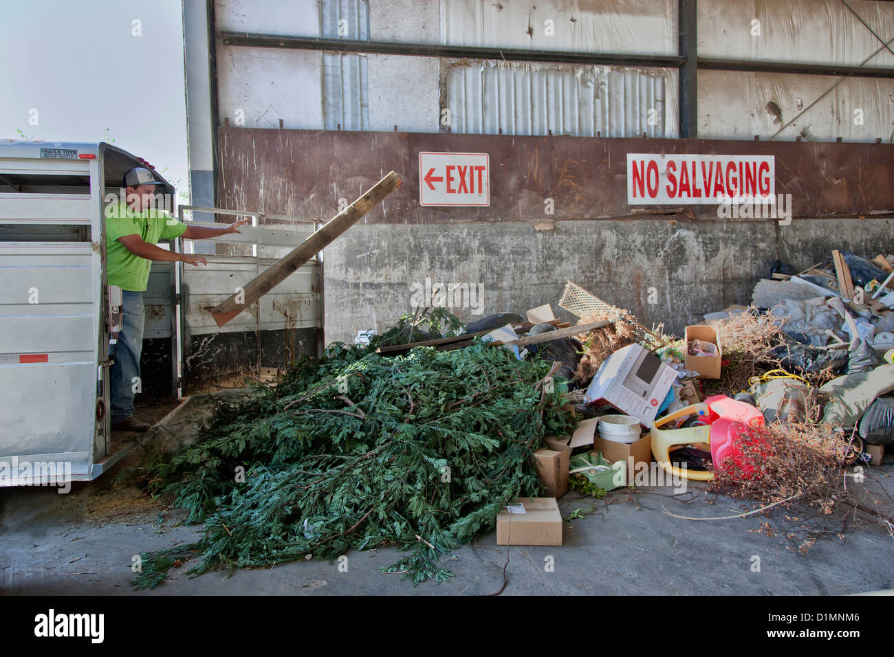 Young adult male dumping trash  & plastics from trailer,  collection site. - Stock Image