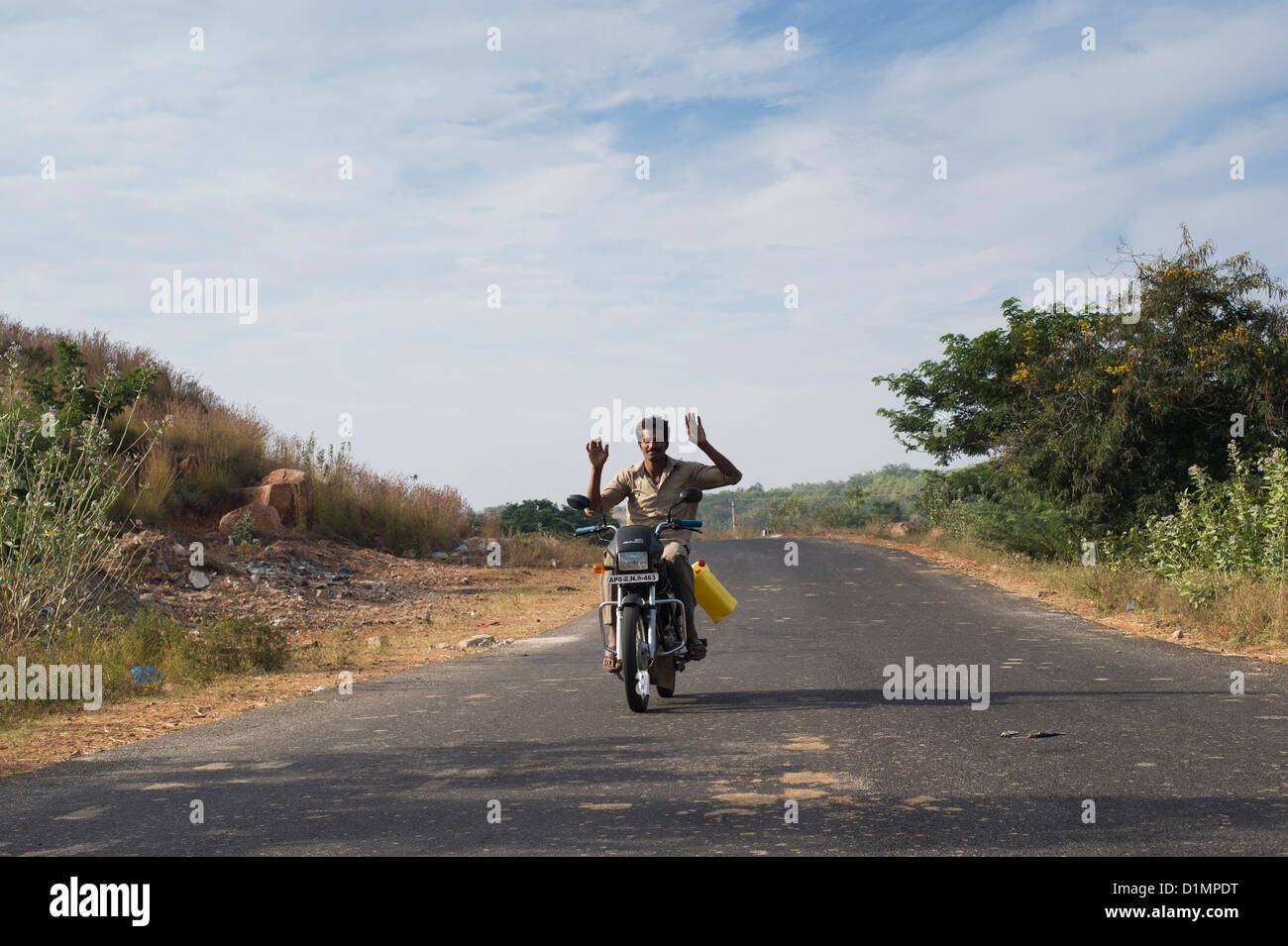 Indian man driving his motorcycle with no hands on the handlebars. India - Stock Image