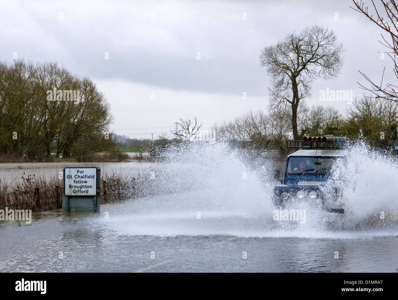Motorists braving floods at Melksham in Wiltshire after heavy rains caused the River Avon to burst its banks - Stock Image